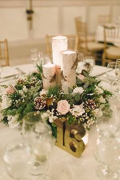 Aspen and pine cone table centerpieces with candles are pretty much perfect for a winter wedding.