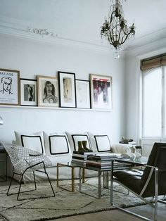 lined artwork on shelf, white walls, architectural mouldings, crystal chandelier, Bertoia wire chair, white rug