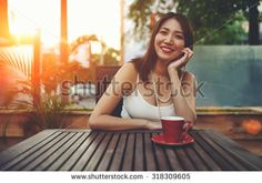 Portrait of a smiling beautiful asian woman enjoying free time while sitting in coffee shop exterior terrace with beautiful sunset on background, wonderful young female posing for the camera in summer