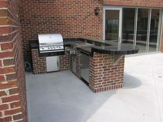L-Shaped Brick Outdoor Kitchen  With a grill, refrigerator, and burners, this L-shaped outdoor kitchen is perfect for cooking outside. Brick was used on the base of the structure to match the brick on the existing home. The black tile countertop complements the home's black details.
