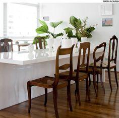Em sua mesa de jantar neutra, combine cadeiras diferentes umas das outras. Para que o resultado seja harmônico, unifique o material. Por exemplo, use determinado tom de madeira. Projeto de Mariana Tassinari, Bruna Albuquerque e Lívia Ribas.