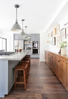 Rustic inspired kitchen with dark wood floors, a light gray island, and gray pendant lights and wood barstools