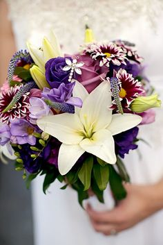 wedding bouquet has jeweled dragonfly. beautiful purple flowers. looks like a wildflower bouquet