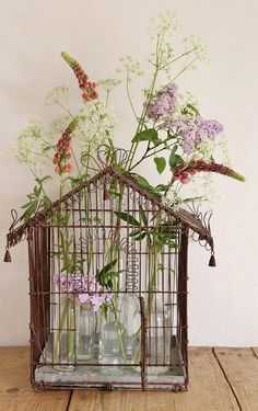 birdcage centerpiece or summer indoors...first put a number of glass bottles with water in the cage and then stick your the flowers from above through the bars of the cage into the bottles...pretty centerpiece for an outdoor garden party or a pretty way to display flowers from your garden inside the house