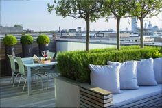 Rooftop in Bermondsey | Decked rooftop with built-in seating area and views across London | Charlotte Rowe Garden Design