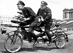 """chicago police officers frank folsom, left, and robert williams rehearse an act on a 15-gun """"sniper bike"""" for the police and fire thrill show in july 1941."""