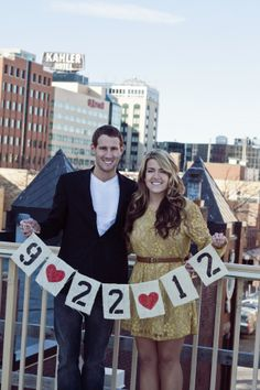 couple holding diy wedding date banner and city skyline in background | rochester mn engagement session | photo: emilybougheyphotography.com