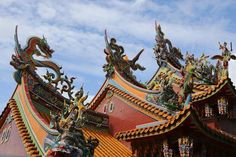 Dragons coloured scarlet, green and blue adorn three pointed temple roofs in Jiufen, Taiwan.