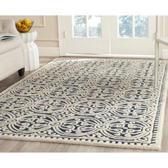 Enhance the decor of any space with this handmade wool rug that features an eye-catching geometric pattern. The navy blue rug has a durable cotton-canvas backing that ensures its longevity, and it is made of extra-soft wool to ensure its comfort.