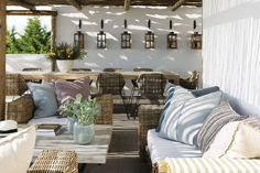 Lanterns line the wall over the dining area of this outdoor living space!