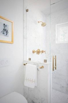 A brass and lucite towel holder lines a glass and marble shower enclosure filled with white marble tiles lined with a brushed brass shower kit alongside a white marble herringbone tile shower floor. Bathroom Ideas Uk, Bathroom Renovations, Bathroom Inspiration, Modern Bathroom, Bathroom Organization, Bathroom Pics, Gold Bathroom, Bathroom Small, Master Bathrooms