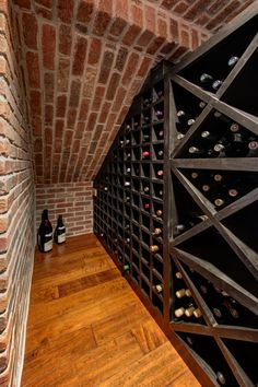 A small basement nook is put to use as a wine cellar, featuring a wall-to-wall wine rack and exposed red brick walls. Wide-plank wood floors complete the look of the space.