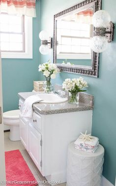 Gorgeous blue green powder room makeover {before & after) . I love how the blue paint color (drizzle - SW 6479 by Sherwin-Williams - ) coordinates with the white and coral accessories.