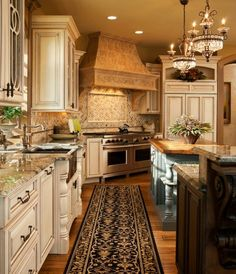 A corner kitchen with a runner along the floor in front of the sink and painted cabinets in cream and muted teal. This example mixes elements of English and French country designs with the crystal and iron light fixtures above the kitchen island and the stone and tile elements around the main cooking area.: