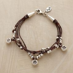 """FORGET-ME-KNOT BRACELET -- Sterling silver seeds are knotted amid a smattering of full-blown blossoms on multiple strands of waxed brown linen. Handcrafted in USA with a lobster clasp. Approx. 7-1/4""""L."""