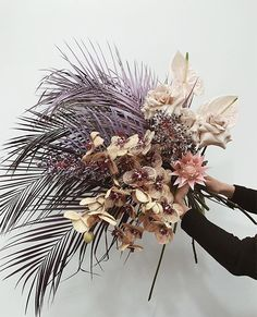 Summery palm leaf and orchid bouquet. Modern bouquet with pink protea, tan and lavender.