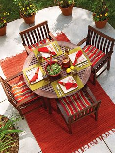 AFTER: Patio Perfect for a Family Dinner [bold colors, outdoor rug, pots with colorful flowers--so welcoming!]