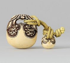 A well carved ivory netsuke of a mokugyo, by Gyokushû. Late 19th century. The handle in the shape of two dragons holding a pearl in their mouths, their scaly bodies rendered as a decorative pattern. Signed Gyokushû. En suite a miniature version of the netsuke as ojime with a spurious signature reading Gyokushû but written with a different second character.