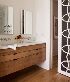 Crafted from richly-grained oak, this custom vanity brings depth and character to an all-white bathroom. Simple cut-outs, in lieu of traditional door hardware, look modern and make it easy to access e