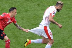 Albania's midfielder Ergys Kace (L) pulls down the shorts of Switzerland's midfielder Valon Behrami during the Euro 2016 group A football match between Albania and Switzerland at the Bollaert-Delelis Stadium in Lens on June 11, 2016. / AFP / Denis CHARLET