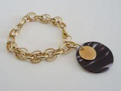 Pulseira de corrente dourada com pingente de madre pérola animal print (zebra) e moedinha dourada. R$22,00