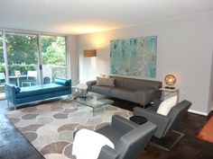 The neutral gray and white living room is given a calm feel with blue accents.  The Domain area rug adds texture while also pulling together the seating area.
