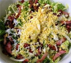 Salade Frisée aux Lardons (French or Belgian custom salad with bacon that usually uses pork belly fat instead of bacon and a fried or poached egg. This is more Americanized.) Ingredients:Endive, bacon,hard boiled egg,Vinaigrette  Preparation - Prepare endive and put on plate, grate 1 hard boiled egg ontop, fry bacon, drain & crumble on top. Add vignaigrette.