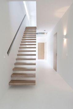Moderne zwevende trap met houten treden en ingefreesde leuning in de muur