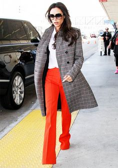 Victoria Beckham wears a plaid coat with orange trousers and retro sunglasses