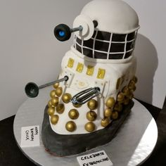 Smoochie's Creations - Neapolitan Dr. Who, Dalek Cake - Layers of Strawberry cake, strawberry freezer jam filling, vanilla cake, chocolate butter cream and chocolate cake covered with vanilla buttercream. Decorated with fondant and Lindor chocolates painted with gold luster dust. Eye stock, Suction cup and blaster gun are made from gum paste. Base is made from rice crispy treats and there is another layer in the middle to help with stability.