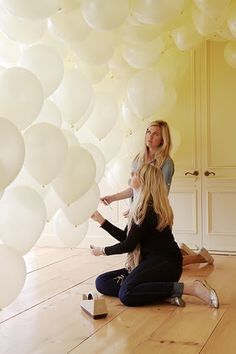 taping the strings at various heights to create a wall of balloons.  Instant backdrop for photos