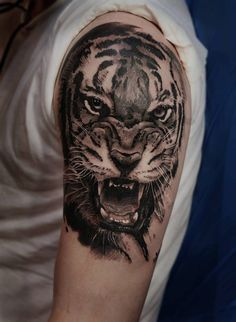 Realistic tiger tattoo on the left upper arm and shoulder.
