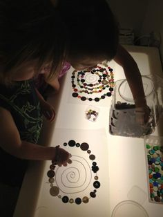 Light Table Mandalas with various materials. We've used buttons, glass beads, shells, and bottle caps.The children are constantly looking for more small material collections to use in their Mandalas. A mandala ritual can be a very empowering...