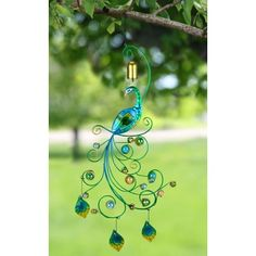 Enhance your outdoor space with the proud flair of this glorious peacock garden bell! The decorative hanging is adorned with luminous glass accents and hand painted metal details. 10'w x 30'h.