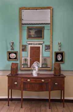 George Washington's sideboard, looking glass, knife cases, and Argand lamps are installed in the northeast corner of the room, along with 18...