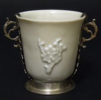 BLANC DE CHINE. Transitional - Kangxi. 17th Century.A Blanc de Chine porcelain beaker, Transitional-Kangxi. Decorated with three applied prunus spriggs. The silver mount probably later. Tiny mark to the base of the highly cleaned silver. Provenance : S.Marchant & Son. Illustrated in : Blanc de Chine (S.Marchant & Son, London 2006) Page 149 Item 115. R and G McPherson dealers in antique Chinese porcelain