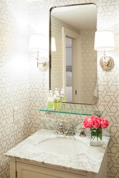 An elegant oval mirror gives the linear bathroom a hint of curves. Satin-nickel light fixtures on either side of the oval mirror bring additional softness to the room.