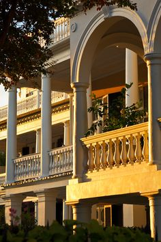 Piazzas of antebellum homes face Charleston Harbor, catching cool breezes and sunset's golden hues.