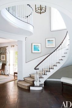 "In the stately circular stair hall, the photographs are from Ed Ruscha's ""Nine Swimming Pools"" series; the walls are painted in Farrow & Ball's All White 