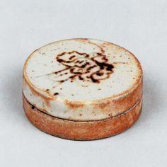 桃山時代、天正年間(1573~92)から文禄・慶長年間(1592~1615)にかけて、現在の岐阜県土岐、可児の二郡に散在する美濃の窯では、志野、黄瀬戸、織部などの、優れた香合が焼かれた。なかでも志野の一文字といわれる香合は、作行きが優れていることで声価が高いものである。この平らな円形の器は、室町時代以来、中国から輸入された堆朱や青貝などの香合に見られ、そうした唐物漆器の香合を倣ったものと思われる。印籠蓋形式にした香合で、身・蓋の合わせ口を除くほぼ全面に長石釉がかかっている。蓋表に蝶のような文様を、鉄絵具で絵付けした優雅な作行きで、側面から高台にかけての釉肌には志野独特の火色が鮮やかに現れている。高台はきわめて低く、比較的大きく丸い。浅く削り込まれた高台内に、置き台の跡が輪形に残っている。志野の一文字の香合の中でも、見どころが多い優れた香合である。