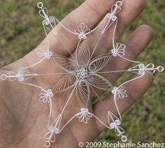 Paper filigree snowflake with looping and silver metallic acid free paper