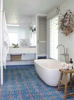 Patterned colourful floor tiles in otherwise white bathroom. Like the simple big mirror and the bathtub. Clean lines.