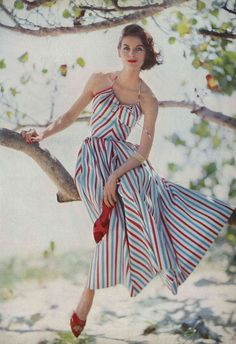 Anne St-Marie is wearing a one piece halter top satin striped dress by Hope Skillman, photo Roger Prigent. Vogue May 1957 fashion style sun dress 50s color model print ad