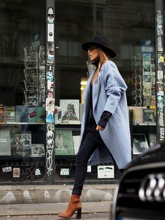 chic street style: black outfit with a hat and a grey coat, paired with brown boots
