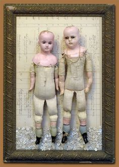 Gesso frame, antique French ledger pages, antique shell buttons, antique straw-stuffed wax over dolls, with glass eyes and original jewelry.