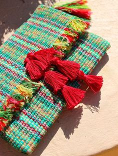 Artisan-made woven clutch made from Balinese Ikat textile.Beautified by golden string and handmade tiered red tassels, this clutch is precious piece to wear th