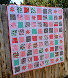 The Postage Stamp Stacker Quilt is a fun twist on your typical charm squares quilt. The use of fusible applique infuses the square design with a fresh breath of spring flowers.