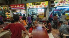 Local people queue at street food stalls in a hawker food market in downtown Singapore. Photo: iStock