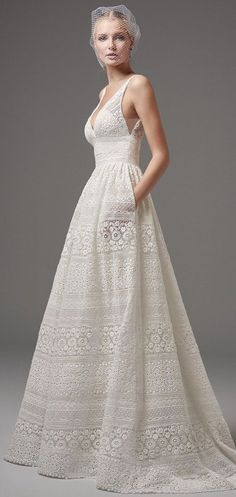 boho inspired lace wedding dress featuring sheer pockets and patterns of eyelet lace, floral motifs