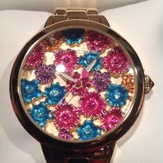 Betsy. johnson Rare flower watch Vibrant blooms and warty to Betsy Johnsons lovely watch. Gold tone dial with pink flowers, crystals accents, luminous hands and signature fuchsia heart second hand. Round case, 42mm water resistant to 30 meters. Betsey Johnson Accessories Watches